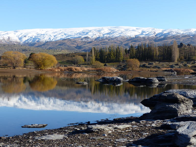 Snow covered mountain range reflected in lake at Butcher's Dam, Central Otago, New Zealand royalty free stock photos