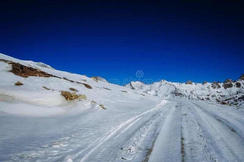 Snow covered mountain road on winter day,. Eastern Tibetan Plateau stock image