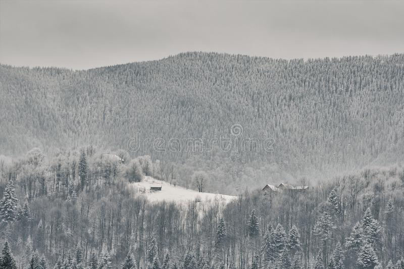 Snow-covered mountain slopes. Small house in the distance.  royalty free stock images