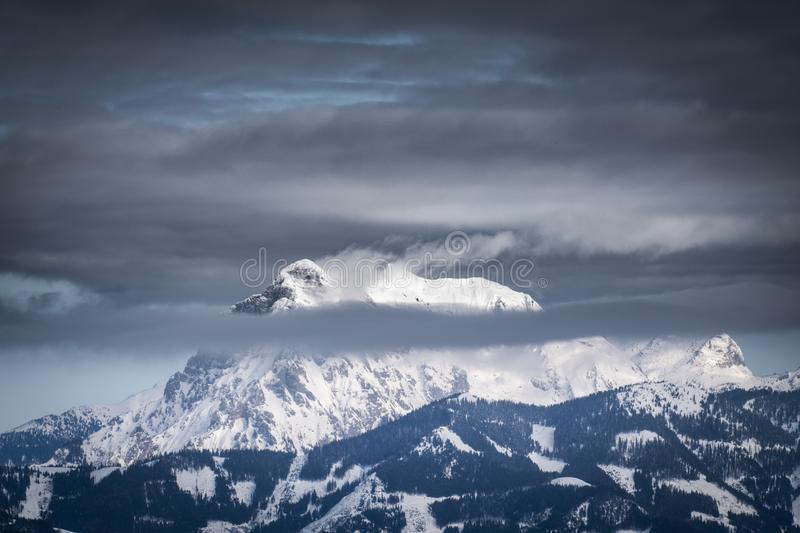 Snow covered mountain summit Hochtor in winter with some clouds. View from Scheibelalm in holiday resort Hohentauern to Ennstaler Alps with snow covered mountain royalty free stock photo