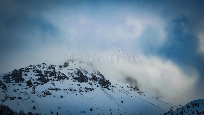 Snow Covered Mountain Under Cloudy Blue Sky stock image
