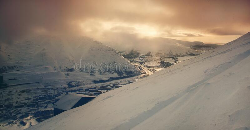 Snow covered mountainside, city below, and sunset sky above with clouds.  stock photos