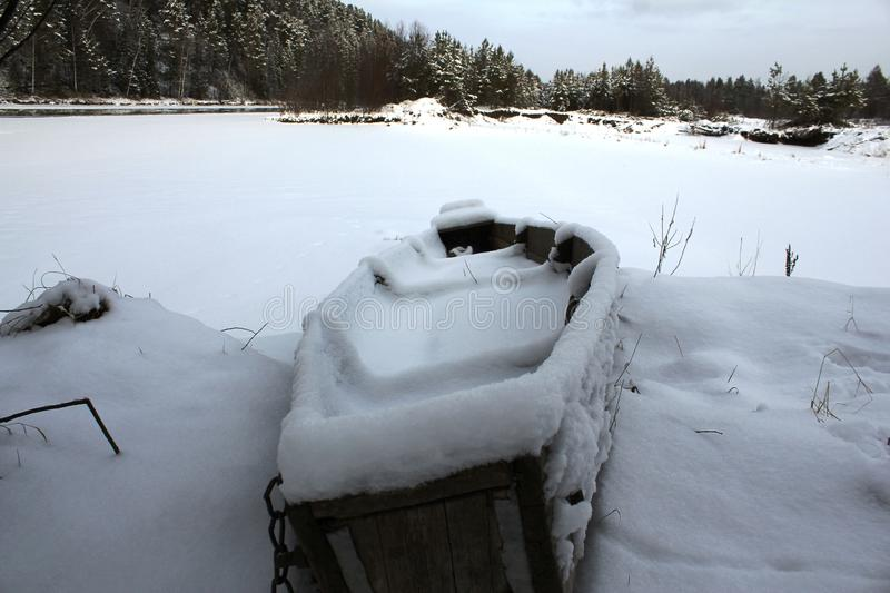 Snow-covered old boat on the bank of a frozen river. stock image