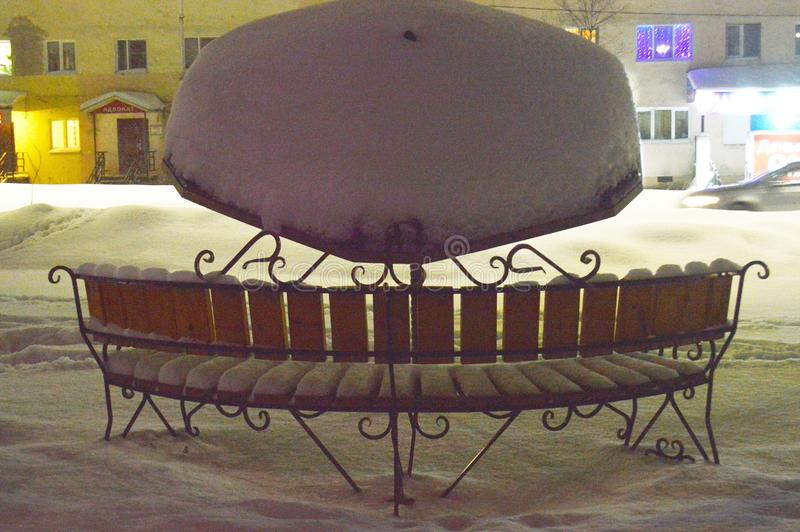Snow-covered outdoor bench at night. royalty free stock photo
