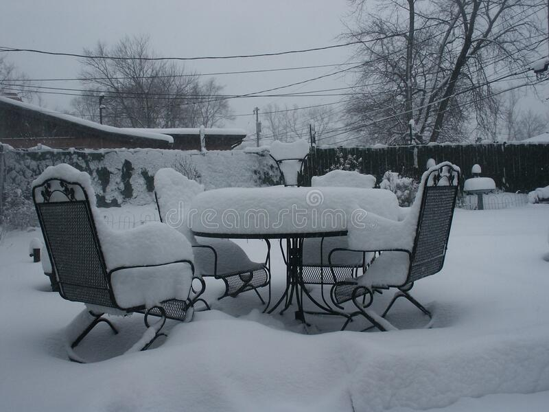 Snow covered patio furniture royalty free stock image
