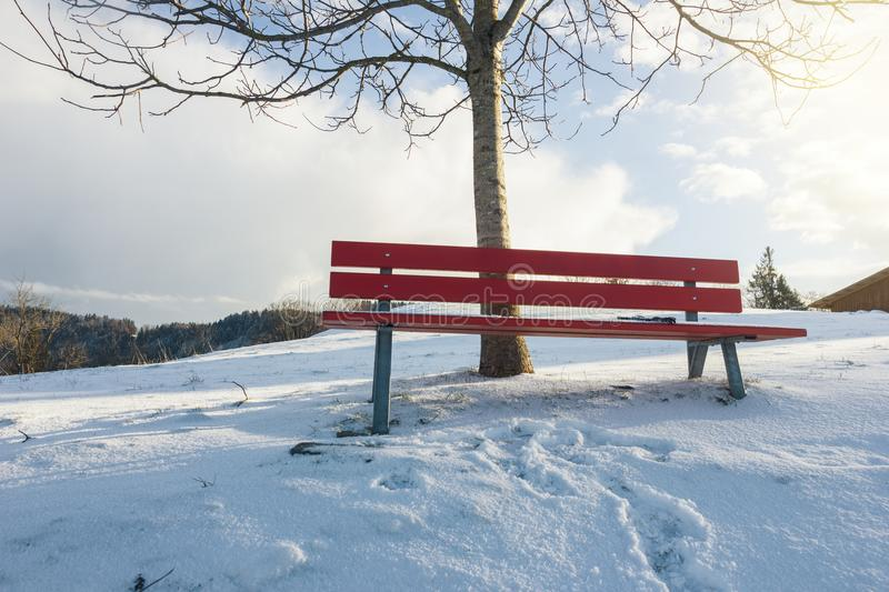 Snow covered red bench in front of winter landscape with snow ma stock images