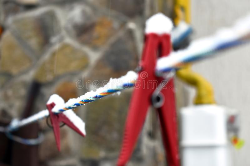 Snow-covered red clothespin on the colorful line, close-up. A macro picture of the red clothespin on the colorful line. Stone wall in the background stock photography