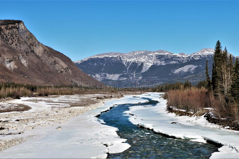 Snow covered river with mountains in background royalty free stock image