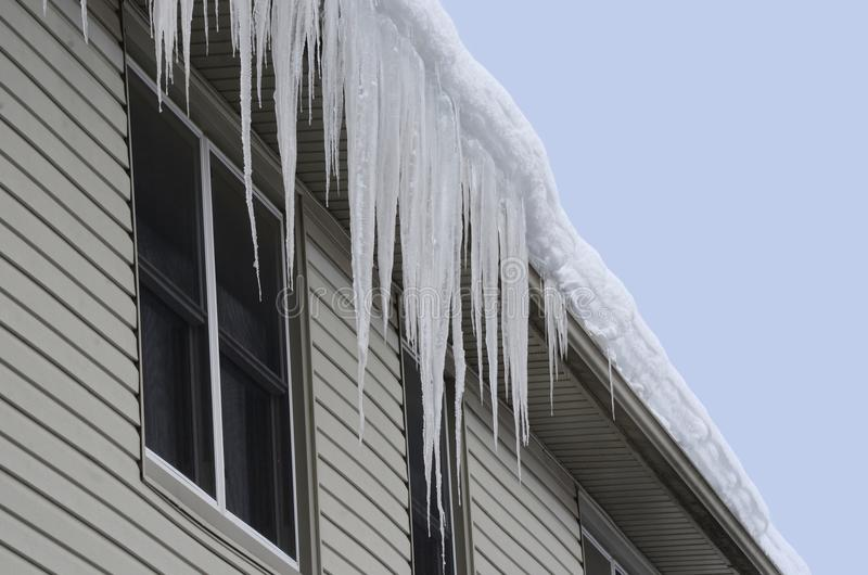 Snow covered roof with long icicles hanging over the eaves-through stock photo