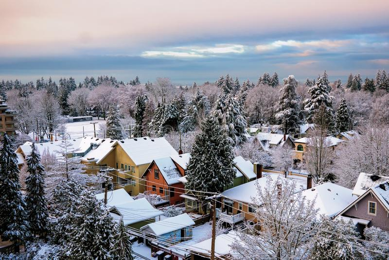 Snow covered roofs and distant trees provide a colorful image of a residential area in Vancouver. A wintry day and distant views over the Strait of Georgia and stock image