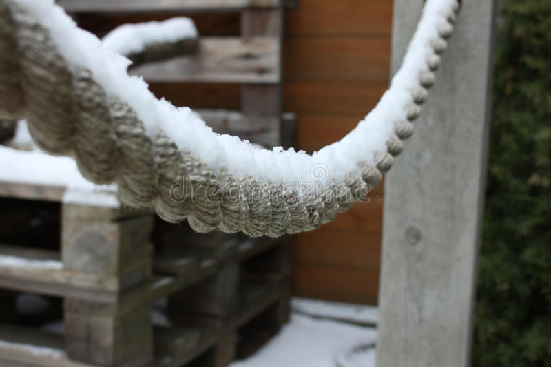 Snow covered rope and wooden pallets royalty free stock photos