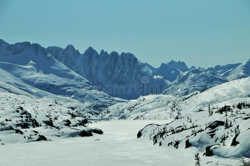 Snow covered sawtooth mountains and frozen lake in British Columbia stock photos