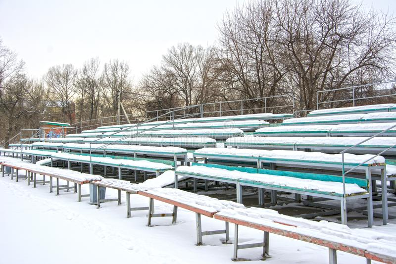 Snow covered tribune in a deserted park. Winter. Russia stock photo