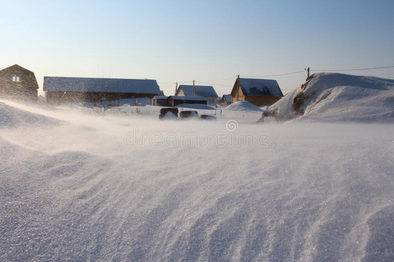 Snow-covered village houses in snowdrifts royalty free stock photos
