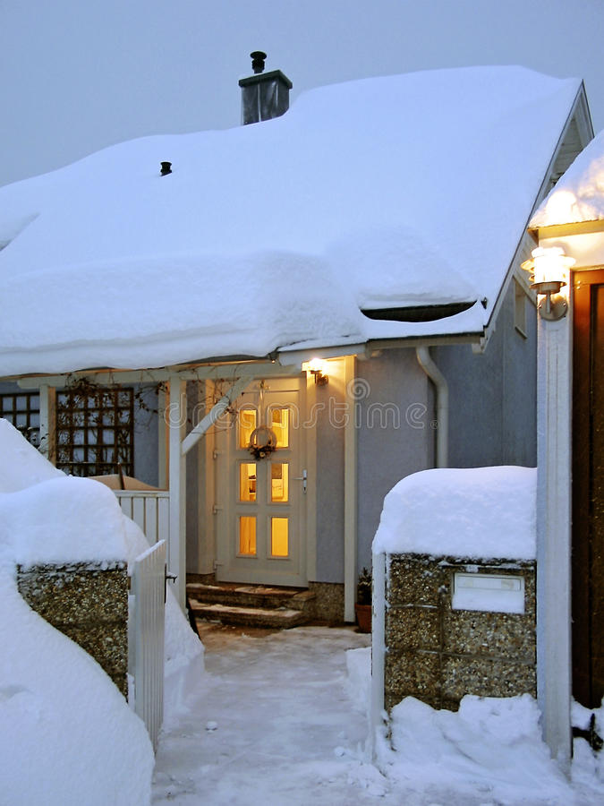 Snow-covered winterly house entrance. With light from inside at twilight, Austria stock image