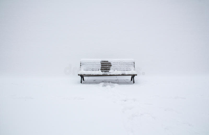 Snow-covered wooden bench with an imprint of someone. Who had been sitting in the middle; winter has gone stock image