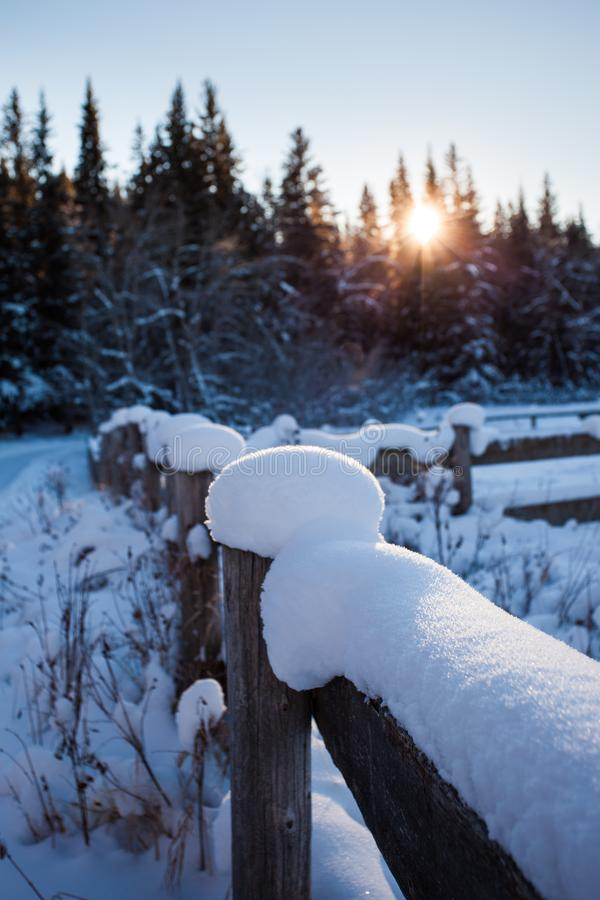 Snow covered wooden fence on a cold winter`s day royalty free stock photo