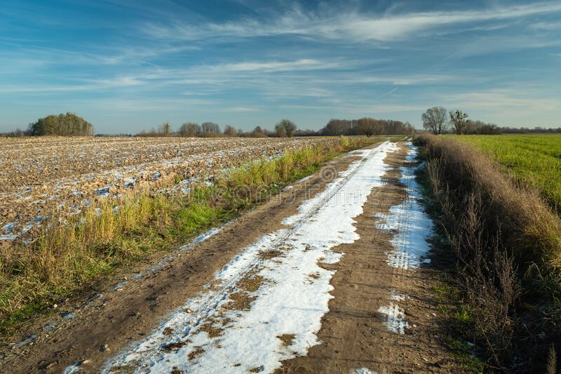 Snow on a dirt road through fields, horizon and clouds on a blue sky in Nowiny, Poland stock images