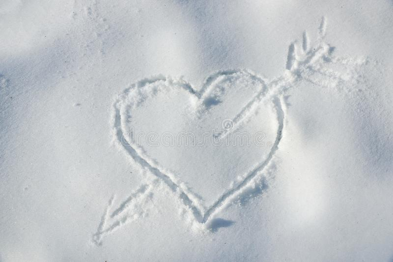 Heart pierced by an arrow in the snow drawing a valentine stick stock photos