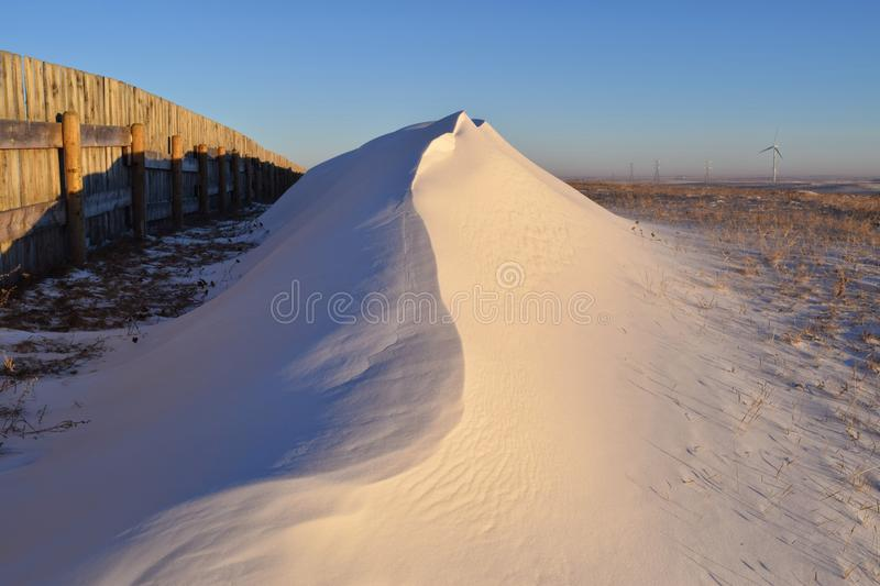The Snow Drift. Spine of a Snow Drift next to a snow fence stock images