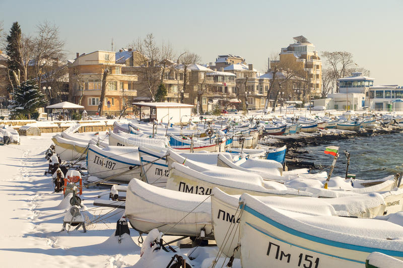 Snow drifts on the fishing boats on the docks of Pomorie, Bulgaria. Pomorie - ancient Bulgarian seaside town famous discoveries of ancient Slavic settlements royalty free stock photo
