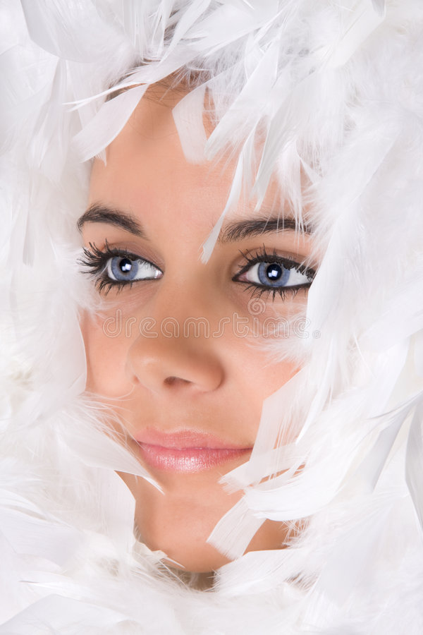 Snow fairy. High-key portrait of an attractive young woman in snow feathers royalty free stock image