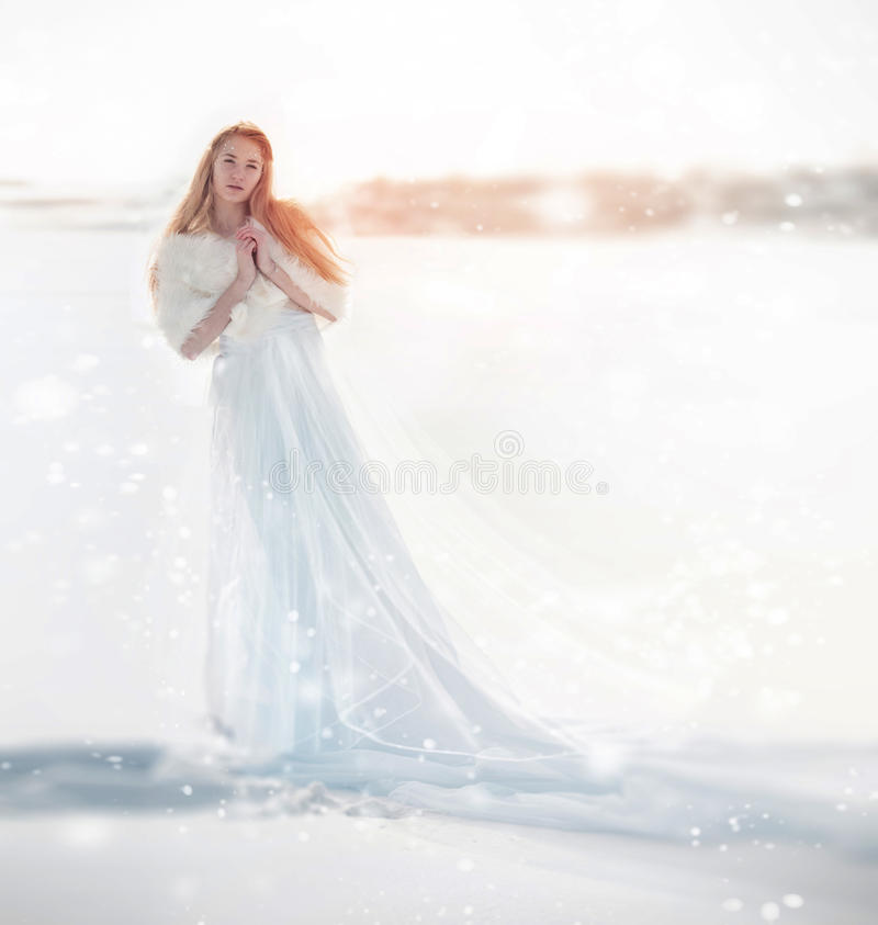 Snow fairy, the snow Queen. Girl in a white dress standing in the snow, wonderful way. Christmas fairy. stock photos