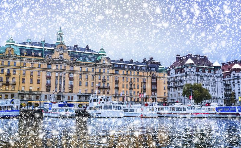 Snow falling over Stockholm harbor Swedish historical architecture. Shot of Stockholm harbor during snowfall showing beautiful Swedish architecture and boats royalty free stock photo