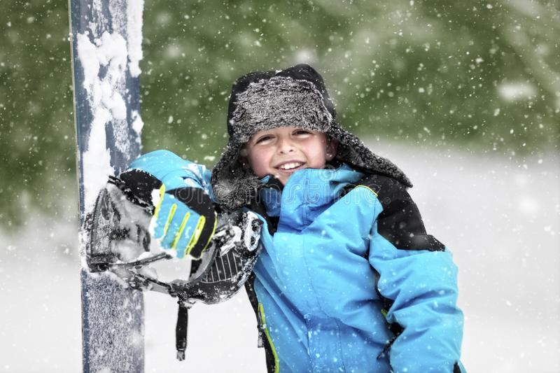 Snow falling on boy leaning on a snowboard stock images