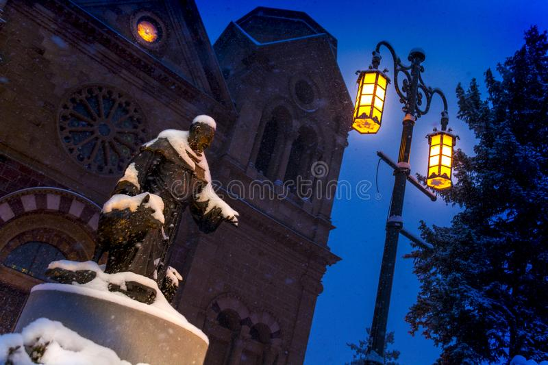 Snow Falls Heavily on this Night Time scene of the Basilica of St. Francis and St. Francis of Assisi Statue in Santa Fe New Mexico. This picturesque night tiime royalty free stock images