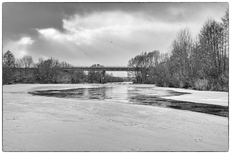 Snow falls over a river covered with ice at the edges of the banks. royalty free stock image