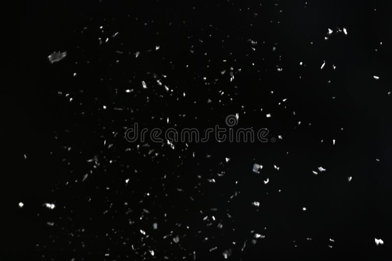 Snow flakes falling on black background. Winter weather royalty free stock photography