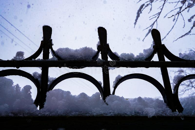 Snow flakes on forged fence, close stock photography