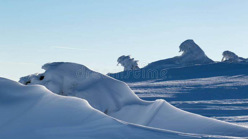Snow formations. Because of the strong winds, in Calimani mountains, Romania, there are all kind of snow formations like this ones in the picture that make you stock photography