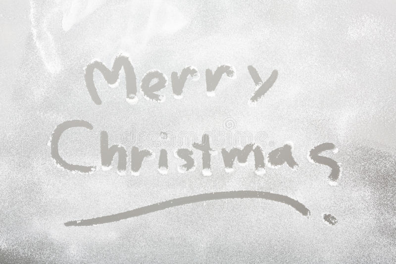 Snow on the frozen window with word Merry Christmas. Christmas background. Snow on the frozen window with word Merry Christmas stock images