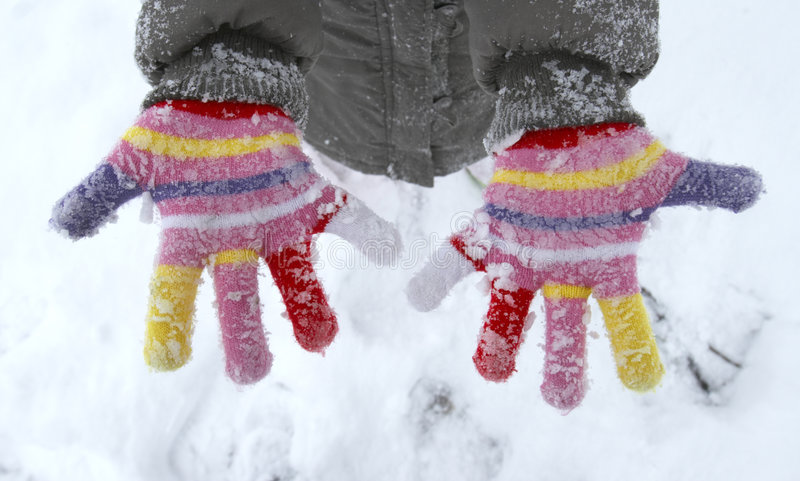 Snow fun 3. Close up of colorful gloves covered with snow royalty free stock images