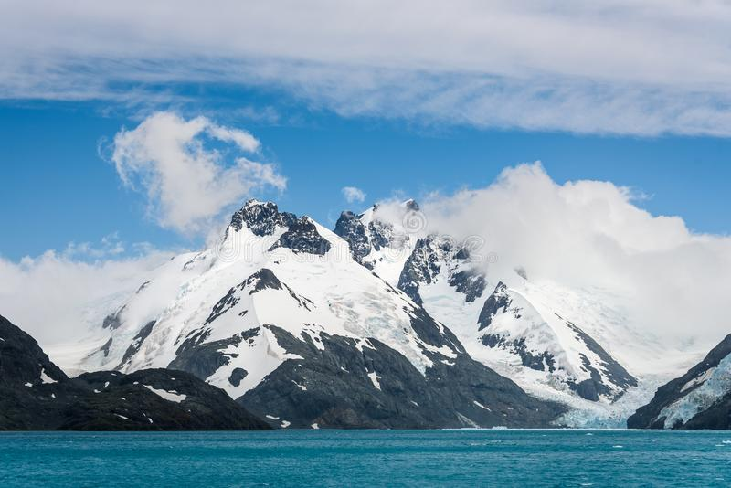 Snow and glacier ice covered rocky mountain peaks, with low white clouds, glacier melt blue water, and blue sky and white clouds a. Bove, Drygalski Fjord, South stock images