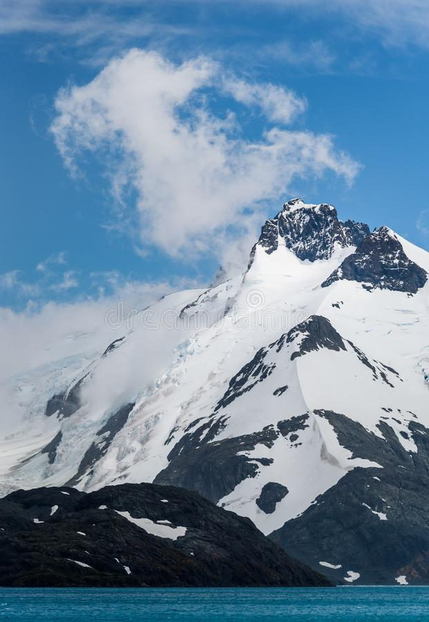 Snow and glacier ice covered rocky mountain peaks, with low white clouds, glacier melt blue water, and blue sky and white clouds a. Bove, Drygalski Fjord, South stock photos