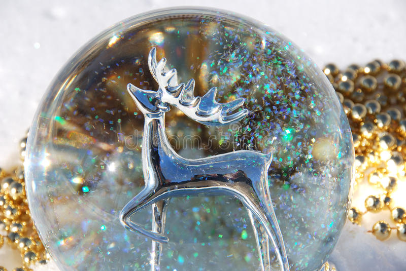 Snow globe. A silver reindeer in a snow globe stock image