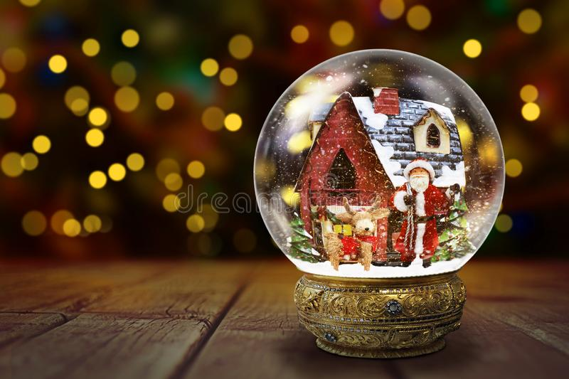 Snow Globe Against Christmas Lights Background. Snow globe against blurred Christmas tree lights background with bokeh, on a wooden boards royalty free stock photo
