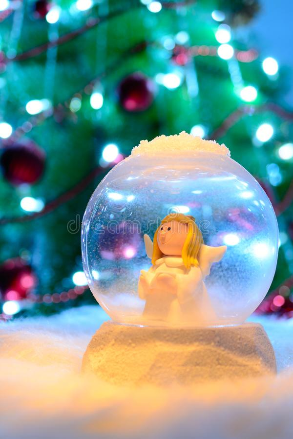 Snow globe with angel inside on a background of decorated fir. Snow globe with an angel inside on a background of decorated fir stock image
