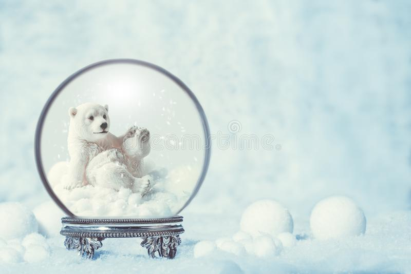 Winter Snow Globe With Polar Bear. Snow globe on an antique silver stand in snowfall for Christmas holidays with polar bear figure royalty free stock images