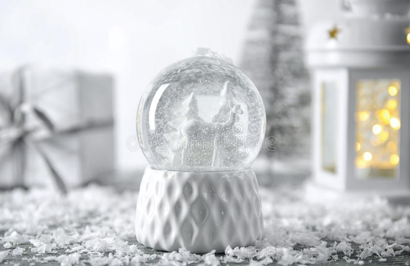 Snow globe with Christmas decorations. On table royalty free stock image