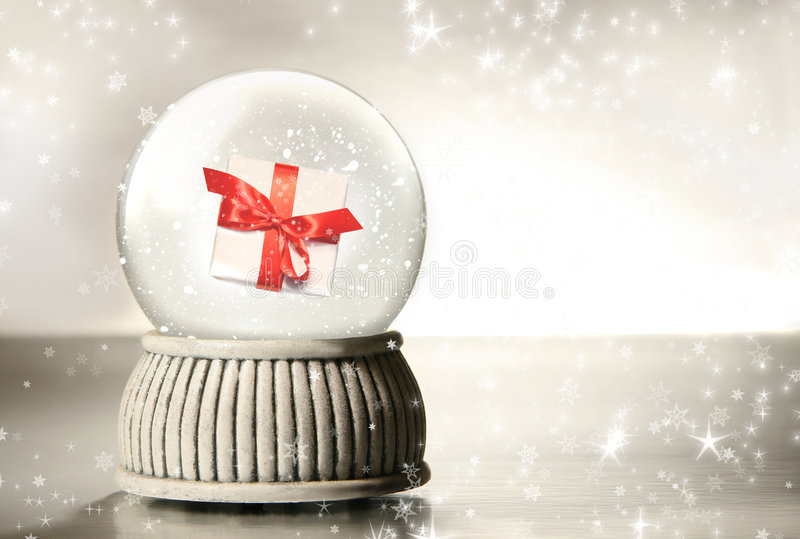 Snow globe with gift against silver royalty free stock photography