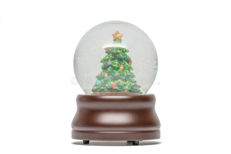 Snow globe of green Christmas tree with glittery sparkles visible - brown wood base -  isolated on white royalty free stock images