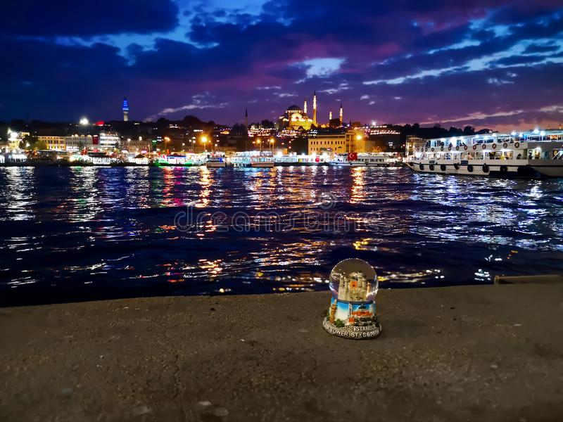 Snow globe of Istanbul against the night landscape of the Golden Horn Bay and lights of Suleymaniye Mosque. The concept of royalty free stock photo