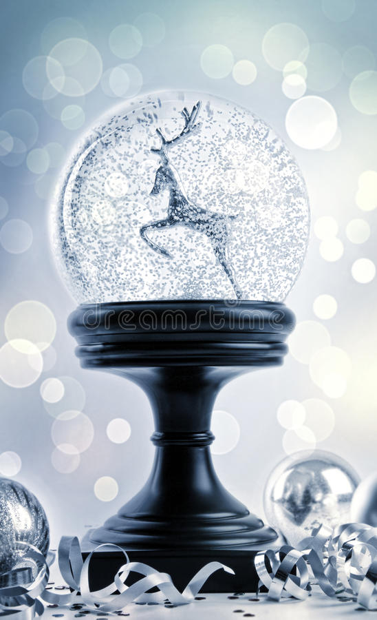 Snow globe with ornaments stock photography