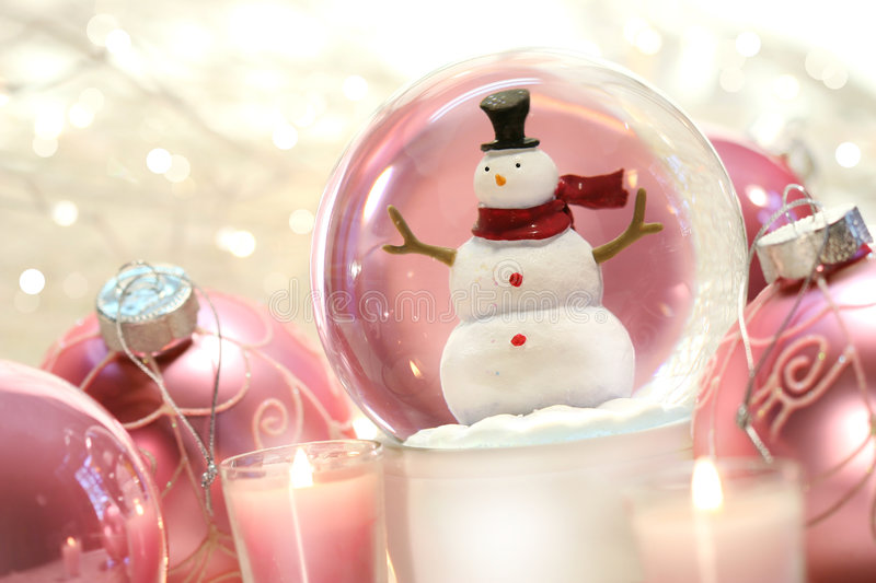 Snow globe with pink balls. Snow globe with pink christmas balls and white lights in background