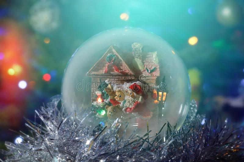Snow globe with Santa, child and house. Long exposure time. Santa Claus with a child next to the house and a street lamp. Musical snow globe with illumination stock photos