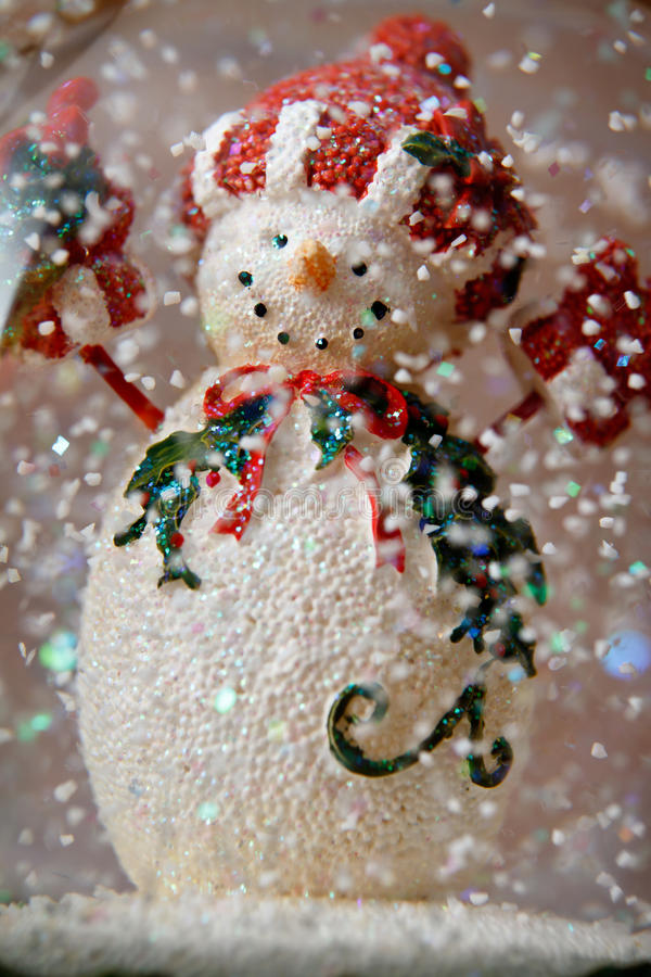 Snow globe snowman. With falling flakes royalty free stock photography